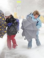 Kyrsten Burns, 10, and Aislynn Boor, 7, fight wind gust of more than 30 mph and snow as they walk home from Wiley Elemetary School Tuesday. (Travis Morisse)