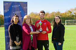 Lincoln City's Tom Pett has been presented with his PFA Bristol Street Motors Fans Player of the Month award for September.  Pictured is, from left, Bristol Street Motor's marketing graduate Levina Basra, Lincoln City fan Steph Uglow, Lincoln City's Tom Pett and Bristol Street Motors online content manager Tania Henzell.<br /> <br /> Picture: Chris Vaughan Photography<br /> Date: October 18, 2018