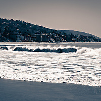 Black and white toned photo of Laguna Beach California coastline with breaking waves and oceanfront buildings along the Pacific Ocean. Laguna Beach is a seaside beach community in Orange County Southern California.