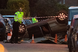 © Licensed to London News Pictures. 22/07/2020. Thame, UK. A police officer stands next to an overturned vehicle on Chinnor Road with a tarpaulin held down by road cones to the side of the vehicle. Thames Valley Police has launched a murder investigation in Thame. At approximately  19:05BST a man was found with injuries in Chinnor Road, Thame. The 20-year-old man was pronounced dead at the scene. Photo credit: Peter Manning/LNP
