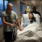 October 30, 2012 - New York, NY : .John Tran, left, walks with his wife, Christine Chin  as she is transported to radiology at The Mount Sinai Medical Center on Tuesday afternoon. .Chin, a liver transplant complications patient, was evacuated during the blackout from New York University Langone Medical Center the previous evening -- down 14 flights of stairs..CREDIT: Karsten Moran for The New York Times