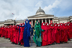 London, UK. 9 October, 2019. Climate activists from the Extinction Rebellion Red Brigade, supplemented by activists dressed in the colours of the Blue and Green Brigades, gather in Trafalgar Square on the third day of International Rebellion protests to demand a government declaration of a climate and ecological emergency, a commitment to halting biodiversity loss and net zero carbon emissions by 2025 and for the government to create and be led by the decisions of a Citizens' Assembly on climate and ecological justice.