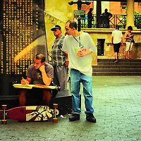 An Asian man looking over an artists shoulder while the artist is drawing in his sketchbook. Chinatown, Manhattan, New York City.