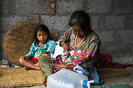 Aastha Baniya (6, in blue) sits with their grandmother Bhagawati Baniya (56) as she bottle feeds her youngest sister Sapana Baniya (2 months) in their temporary home in Chautara, Sindhupalchowk, Nepal on 29 June 2015. The three girls lost their mother during the April 25th earthquake that completely levelled their house. Aastha was buried under the rubble together with her mother but Aastha survived. As their father Ratna Baniya (28) cannot care for the children on his own, SOS Childrens Villages has since been supporting the grandmother with financial and social support so that she can manage to raise the children comfortably and ensure that they will all be schooled. Photo by Suzanne Lee for SOS Children's Villages