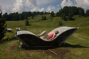 Rest seat made from logs in the Pralongià above San Cassiano-St. Kassian in the Dolomites, south Tyrol, northern Italy. In winter, the Pralongià meadows are the heart of Alta Badia's skiing area.