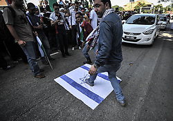 Image licensed to i-Images Picture Agency. 18/07/2014. Kuala Lumpur,Malaysia.Demonstrators step on an Israeli flag as they protest against Israel's military action in Gaza during a demonstration in front of the US embassy in Kuala Lumpur on July 18, 2014.Picture by Mohd Firdaus / i-Images
