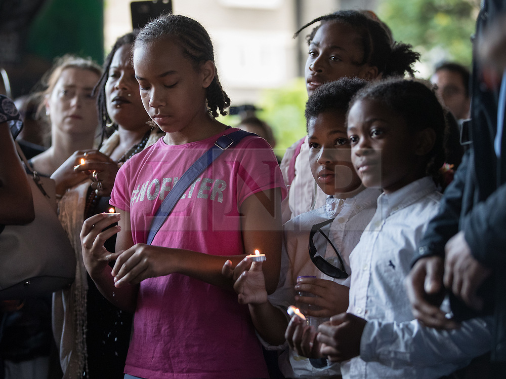 © Licensed to London News Pictures. 14/08/2017. London, UK. Youths hold candles in memory of the victims of the Grenfell tower fire after marching in silence.  The silent march takes place every month to remember the 80 residents of the 24 storey tower block that died in the tragedy on June 12, 2017 in Kensington. Photo credit: Peter Macdiarmid/LNP