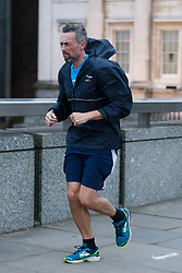 © Licensed to London News Pictures. 09/02/2020. London, UK. A man jogs across London Bridge during windy weather this morning. Rain and windy weather is forecast today as Storm Ciara reaches the capital. Photo credit: Vickie Flores/LNP