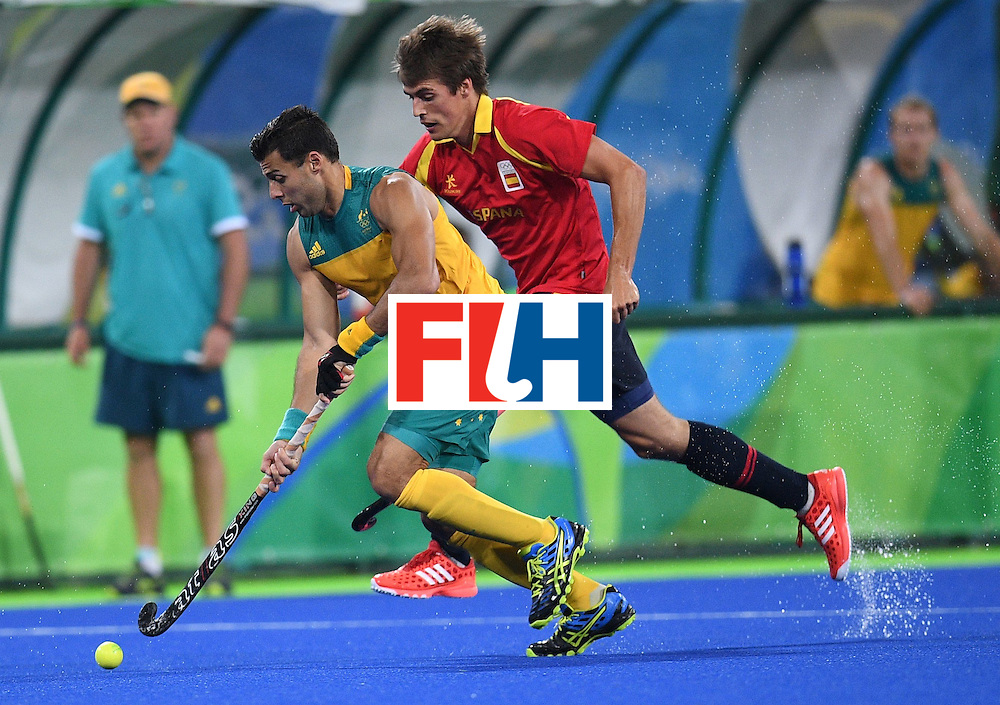 Spain's Alex Casasayas (R) tries to catch Australia's Chris Ciriello during the men's field hockey Australia vs Spain match of the Rio 2016 Olympics Games at the Olympic Hockey Centre in Rio de Janeiro on August, 7 2016. / AFP / MANAN VATSYAYANA        (Photo credit should read MANAN VATSYAYANA/AFP/Getty Images)