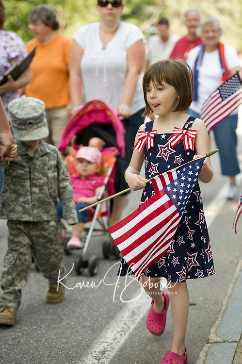 "Wearing her ""stars and stripes"" Tessa Tanner along with family, friends and neighbors walk together from the Community Church to Pine Grove Cemetery for the Memorial Day parade Monday morning.   (Karen Bobotas/for the Laconia Daily Sun)"
