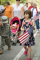 """Wearing her """"stars and stripes"""" Tessa Tanner along with family, friends and neighbors walk together from the Community Church to Pine Grove Cemetery for the Memorial Day parade Monday morning.   (Karen Bobotas/for the Laconia Daily Sun)"""
