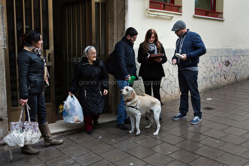 NAPLES, ITALY - 23 January 2014: A dog named Pluto and its owner are stopped by the Municipal Police for an identity check and to make sure the owner carries a bag and shovel to pick up the dog faeces,  in in the Vomero-Arenella neighborhood, where a pilot project to keep streets clean from dog excrements was started, Naples, Italy, on January 23rd 2014.<br /> <br /> The city of Naples started a pilot project in the district of Vomero-Arenella aimed at busting irresponsible dog owners from leaving their pets' feces in the street. Blood samples are being collected from the approximately 8,000 dogs living in the neighborhood of 110,00 inhabitants. (the city of Naples counts a total of 960,000 people and 60,000 dogs). In a few months city street cleaners  will locate the excrements, call the police who will send a sample to a laboratory where DNA will be extracted and compared with the results of blood samples.