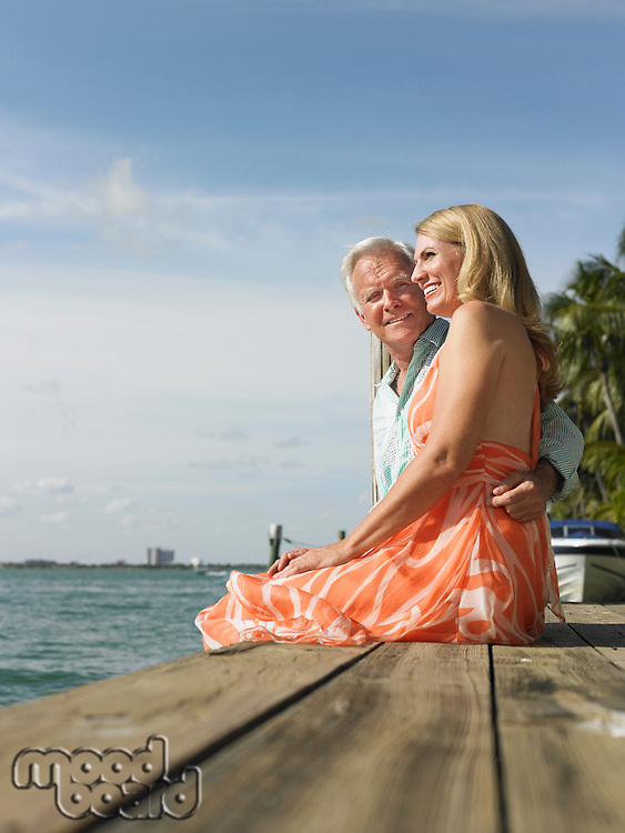 Couple sitting on edge of pier side view