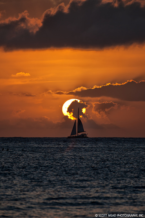 Silhouette of a sailboat on horizon against an orange sky at sunset, Maui, Silhouette
