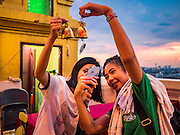 "20 NOVEMBER 2015 - BANGKOK, THAILAND:  Girls take ""selfies"" with an iPhone of the prayer bells they donated at the chedi on top of Wat Saket during the annual temple fair. Wat Saket is on a man-made hill in the historic section of Bangkok. The temple has golden spire that is 260 feet high which was the highest point in Bangkok for more than 100 years. The temple construction began in the 1800s in the reign of King Rama III and was completed in the reign of King Rama IV. The annual temple fair is held on the 12th lunar month, for nine days around the November full moon. During the fair a red cloth (reminiscent of a monk's robe) is placed around the Golden Mount while the temple grounds hosts Thai traditional theatre, food stalls and traditional shows.    PHOTO BY JACK KURTZ"