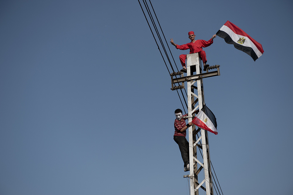 During an anti-Morsi rally near Al-Ittihadiya Presidential protesters climb on a power pole to raise  the Egyptian national flag. Cairo, Egypt, July 2, 2013