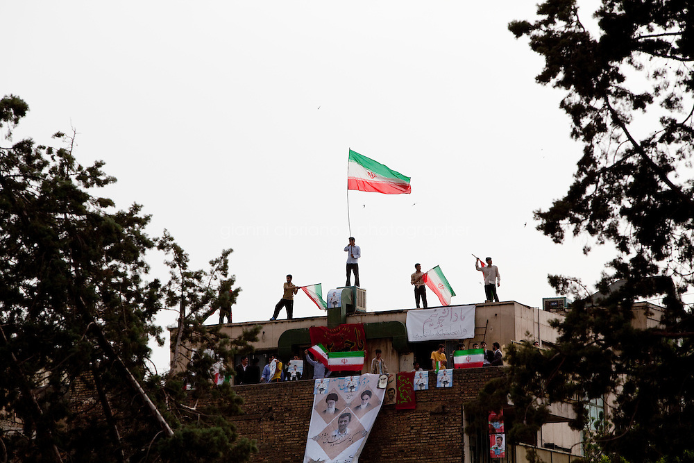 9 June, 2009. Tehran, Iran. Supporters of President Mahmoud Ahmadinejad wave Iranian flags on the roof top of a building near the Heyday Nia Stadium, where a rally for reformist candidate Mir Hossein Moussavi is taking place. Conservative reformist candidate Mir Hossein Mousavi is running against the ultra-conservative current President of Iran Mahmoud Ahmadinejad. <br /> &copy;2009 Gianni Cipriano<br /> cell. +1 646 465 2168 (USA)<br /> cell. +39 328 567 7923<br /> gianni@giannicipriano.com<br /> www.giannicipriano.com