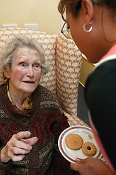Care assistant offering a plate of biscuit to an older woman,