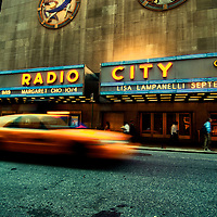 Exterior of Radio City Music Hall with yellow cab driving by. Manhattan, New York City