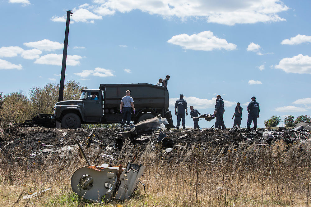 GRABOVO, UKRAINE - JULY 21: Personnel from the Ukrainian Emergencies Ministry load the bodies of victims of Malaysia Airlines flight MH17 into a truck at the crash site on July 21, 2014 in Grabovo, Ukraine. Malaysia Airlines flight MH17 was travelling from Amsterdam to Kuala Lumpur when it crashed killing all 298 on board including 80 children. The aircraft was allegedly shot down by a missile and investigations continue over the perpetrators of the attack. (Photo by Brendan Hoffman/Getty Images) *** Local Caption ***