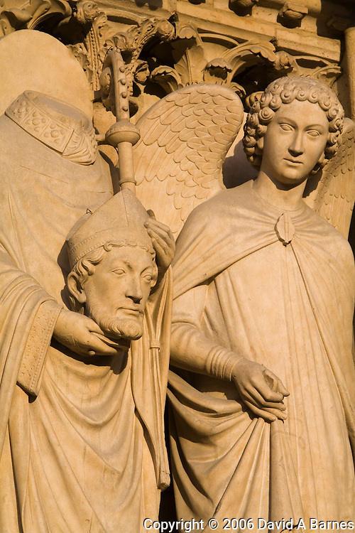 Sculpture on facade of Notre Dame Cathedral of Saint Denis after his martyrdom by decapitation, Paris, France