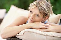 Middle-aged woman sitting on sofa in garden portrait
