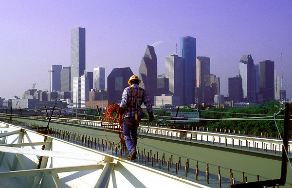Stock photo of a construction worker walking along rebar path with the downtown Houston skyline in the background