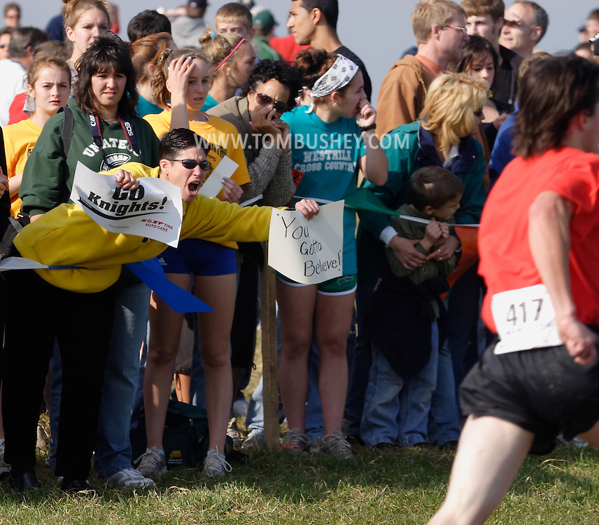 Warwick, N.Y. - Spectators cheer for a runner  near the finish in a boys' race at the New York State Public High School Athletic Association cross country championships at Sanfordville Elementary School on Nov. 11, 2006.<br />