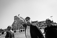 """NAPLES, ITALY - 30 JULY 2018: Roberto Saviano (center), an Italian journalist, writer and essayist is seen here with his police escort by the Vele di Scampia (English: Sails of Scampia), a large urban housing project and one of the poorest and most disadvantaged in the country, here in Naples, Italy, on July 30th 2018.<br /> <br /> Thanks to Roberto Saviano's bestselling book """"Gomorrah"""" — and subsequent film and TV series — the the Vele di Scampia are known worldwide as a hotbed for drugs, prostitution and the mafia. In 2016 the city council announced an ambitious €58 million plan to tear down three of the decaying buildings and convert the fourth into offices.<br /> <br /> After the first death threats of 2006 by the Casalese clan , a cartel of the Camorra, which he denounced in his exposé and in the piazza of Casal di Principe during a demonstration in defense of legality, Roberto Saviano was put under a strict security protocol. Since 2006 Roberto Saviano has lived under police protection.<br /> <br /> Saviano's latest novel """"The Piranhas"""", which tells the story of the rise of  a paranza (or Children's gang) and it leader Nicolas, will be released in the United States on September 4th 2018."""