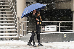 © Licensed to London News Pictures. 28/02/2018. London, UK. Two woman walks around the City of London as heavy snowfall hits central London at lunchtime. The cold spell named The Beast From The East is due to last a few days. Photo credit: Ray Tang/LNP