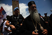 "Serbian Patriarch Irenej guarded by a KFOR soldier at Gazimestan on June 28, 2007. Vidovdan celebration.<br /> <br /> Serbian anniversary celebrations at the site of the 1389 ""Battle of Kosovo"" near Pristina, Kosovo. ...Gazimestan, Kosovo, Serbia."