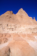 Parched soil and eroded spires under blue sky along the Door Trail, Badlands National Park, South Dakota
