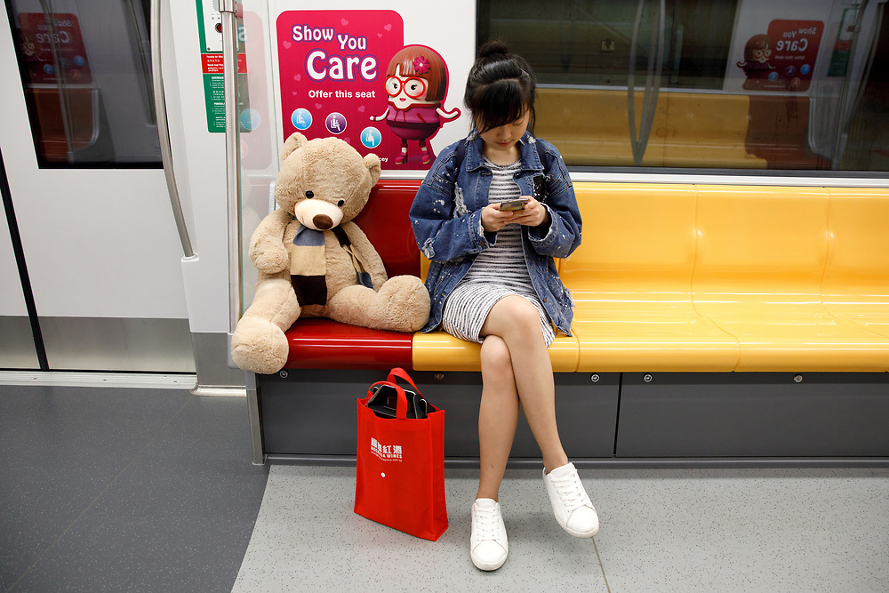 A woman rides the MRT next to a large stuffed teddy bear on the Downtown line, Singapore.