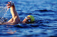 Muscular man in goggles and swim cap swimming in open water