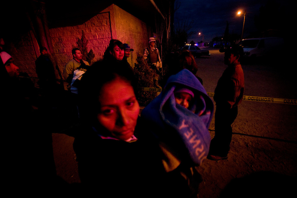 A crowd gathers near the assassination crime scene. Ciudad Juarez has recorded more than 1,500 killings this year..Friday December 19.2008.
