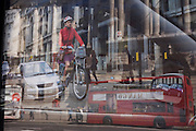 A Transport for London (TFL) poster at a Westminster bus stop shows an oversized cyclist, promoting cycling as alternative mode of transport in London. Reflected in a glass panel is a lady cyclist many times more her actual size than the car next to her in the road and pedestrians waling on pavements. The trick of scale is seen in this TFL campaign for more, safer cycling in the capital which has traditionally been a city for the driver, rathern than for those eager to beat the jams on two wheels.