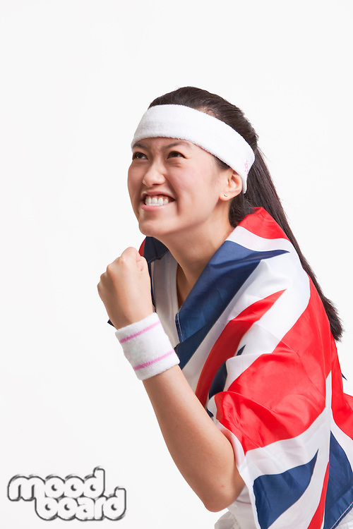 Successful female tennis player with British flag against white background