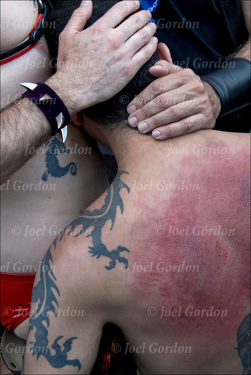 Master / Slave emotional release after cathartic flogging. The flogging brings out a release of emotions usually by a crying. <br /> <br /> Hugging is the &quot;aftercare&quot; where the slave feels safe and protected. Folsom Street East S&amp;M Fair in New York City.