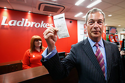 © Licensed to London News Pictures. 02/06/2016. London, UK. UKIP leader NIGEL FARAGE holds up the current odds of Britain voting to leave the EU and places a £1000 bet, during a visit to a Ladbrokes betting shop in the City of London on Thursday, 2 June 2016, to campaign for Brexit ahead of the June 23rd EU referendum. Photo credit: Tolga Akmen/LNP