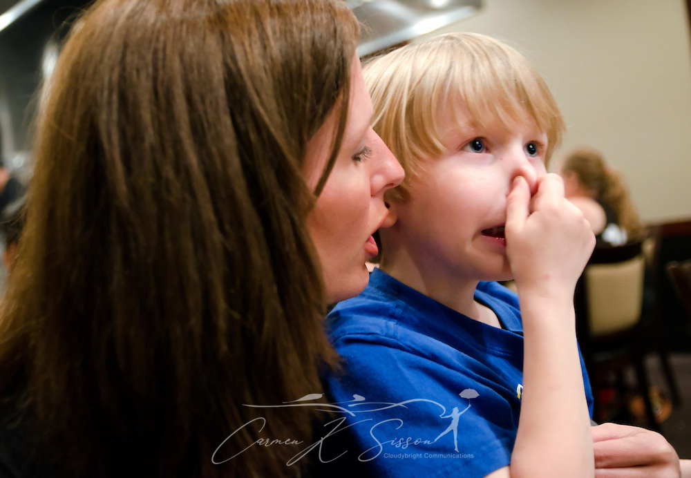 Ashley Birckbichler talks to her son, Elisha, who holds his nose to keep from smelling the food April 19, 2012 at Umi's Japanese Steakhouse and Sushi Bar. Elisha has Asperger syndrome, an autism spectrum disorder. He's particularly sensitive to smells and textures he doesn't like. (Photo by Carmen K. Sisson/Cloudybright)
