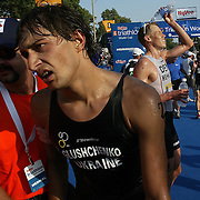 While Andriy Glushchenko, from the Ukrane is helped off the course,  Triathlon winner Rasmus Henning refreshes himself with a bottle of cold water at the HyVee Triathlon World Cup.   The world class event was sponsored by HyVee, a local grocery chain in Iowa.  The elite class of athletes had to compete in blistering heat in Des Moines Iowa in July of 2007.