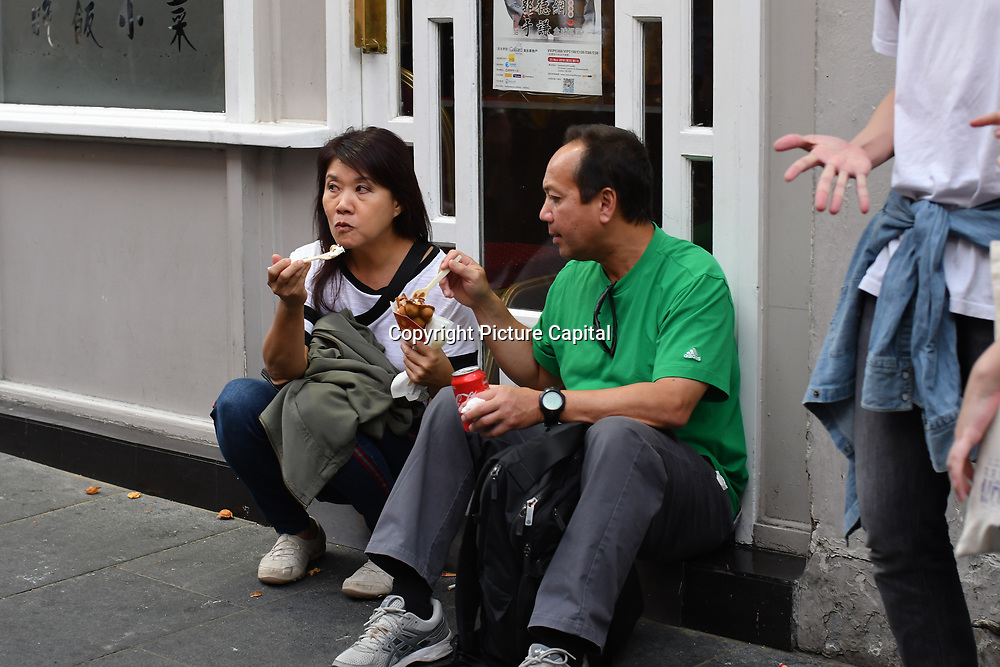 People eating Bubblewrap Waffle at Wardour Street, Chinatown London, UK. 13 October 2018.