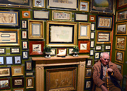 © Licensed to London News Pictures. 10/01/2013. London, USA. A man sits in the gallery of Charles Plante, which specialises in 18th and 19th Centruy watercolour and drawings. The Mayfair The opening day of The Mayfair Antiques & Fine Art Fair. Items on offer include a selection of antiques and works of art, ranging from period furniture, sculpture, oriental artefacts, silver, clocks, calling card cases, objects of vertu and boxes to paintings, ceramics, glass, jewellery, books, oriental carpets, textiles, prints and decorative items. The fair continues until January 13. Photo credit : Stephen Simpson/LNP