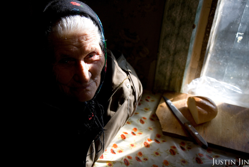 An elderly woman sits with a loaf of bread in Oryol, a poor city in the heart of Russia.