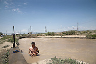 Boy swimming in the water channel by  War memorial site of Sardarapat...Memorial site and the Museum of historical battle with Turkey were built in 1968 and are located about 30 km from Turkish Border..