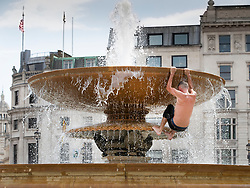 © Licensed to London News Pictures. 26/07/2018. London, UK. A man climbs the Trafalgar Square fountains as London experiences the hottest day of the year so far. Photo credit: Peter Macdiarmid/LNP