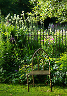 An old metal chair next to a border at Lower Severalls Farmhouse,  Crewkerne, Somerset, UK