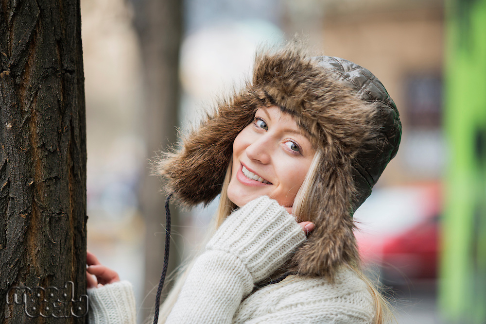 Portrait of beautiful young woman wearing fur hat outdoors