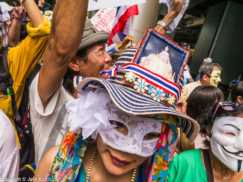 "02 JUNE 2013 - BANGKOK, THAILAND: An anti-government protester with a picture of Bhumibol Adulyadej, the King of Thailand, in her hat, marches with an anti-government protesters. The so called White Mask protesters are strong supporters of the Thai monarchy. About 300 people wearing the Guy Fawkes mask popularized by the movie ""V for Vendetta"" and Anonymous, the hackers' group, marched through central Bangkok Sunday demanding the resignation of Prime Minister Yingluck Shinawatra. They claim that Yingluck is acting as a puppet for her brother, former Prime Minister Thaksin Shinawatra, who was deposed by a military coup in 2006 and now lives in exile in Dubai.     PHOTO BY JACK KURTZ"