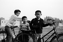 China, Taiyuan, 2008. Friends share classic Flying Pigeon bikes too big for them along this country road near Jingci Park.